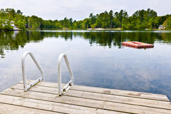Dock on calm lake in cottage country Stock Photos