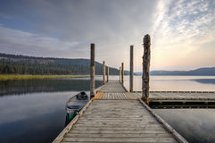 Dock at calm, tranquil lake. The morning light on the dock with a canoe by it on Chatcolet Lake near Plummer, Idaho stock photography