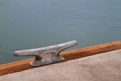 Dock Cleat. Steek Dock Cleat on wood beam next to concrete with a backbround of water Stock Photography