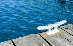 Dock Cleat. Single Dock Cleat, blue water Royalty Free Stock Image