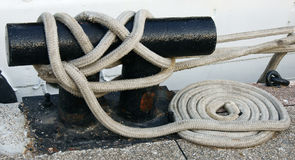 Dock Cleat and white rope. A black cleat with a white coiled rope on a dock Royalty Free Stock Images