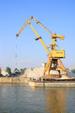 Dock crane. Loading gravel into barges Stock Image