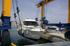 Dock crane elevating a fishing boat Royalty Free Stock Photos