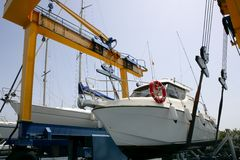 Dock crane elevating a fishing boat Royalty Free Stock Image