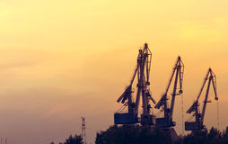 Dock crane silhouettes at sunset Stock Images