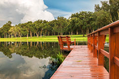 Dock de lac avec la réflexion des arbres et des nuages Photos stock