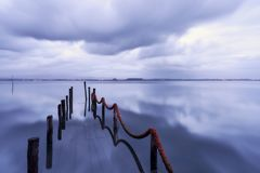 Dock disappear into the lake reflecting waters royalty free stock photos