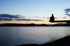 Dock at Dusk. A young person sitting on a dock at dusk, at the fjord in Oslo, Norway Royalty Free Stock Image