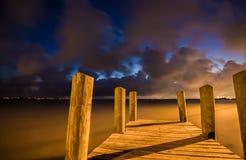Dock en bois de bateau au coucher du soleil avec de beaux nuages Image libre de droits