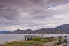 Dock en bois de bateau sur le lac sous les cieux nuageux Photos stock