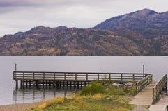 Dock en bois de bateau sur le lac tranquille Photo libre de droits