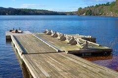 Dock flottant menant à un petit lac Photos libres de droits