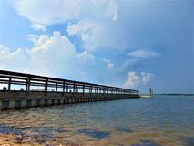 Dock. Framed against a bright blue sky with white clouds, and a dark, choppy sea; Cape May County, New Jersey Stock Images