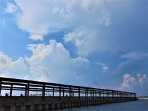 Dock. Framed against a bright blue sky with white clouds, and a dark, choppy sea; Cape May County, New Jersey Royalty Free Stock Image