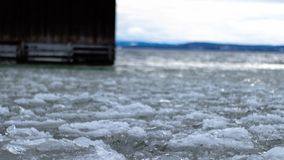 A dock on a frozen lake. A dock on a half frozen lake in winter royalty free stock image