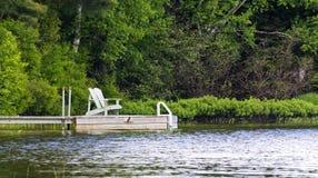 Dock on the lake. Muskoka Chairs on dock at the lake Stock Photos