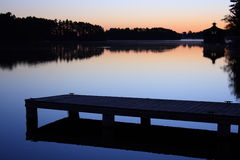 Dock on the lake. Sunrise on a lake with a dock in the foreground and boathouse in the background Royalty Free Stock Photos