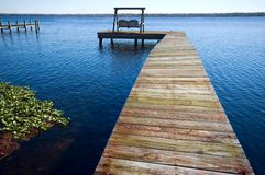 Dock on lake. Wooden dock extending into a blue lake with chairs stock photos