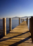 Dock at Lake George. A dock leading its way out to Lake George with mist nestled at the base of the Adirondack Mountains in the background royalty free stock image