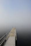 Vanishing dock in lake with heavy fog Royalty Free Stock Images