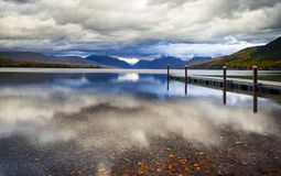 The dock on Lake MacDonald in Glacier National Park. The dock on Lake MacDonald in Glacier National Park in Montana, USA on a n overcast day in late afternoon Stock Photo