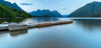 Dock on Lake Surrounded by Mountains Royalty Free Stock Photos