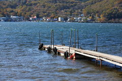 Dock on lake. Wooden dock extending into a blue lake Stock Image