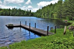 Dock at Leonard Pond located in Childwold, New York, United States. A dock at Leonard Pond located in Childwold, New York, United States in the Adirondack royalty free stock photo