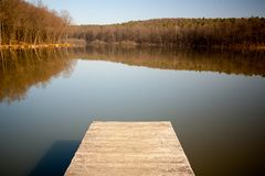 Dock. Lonely wooden dock on a sunny day in autumn with calm water Stock Image