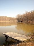Dock. Lonely wooden dock on a sunny day in autumn with calm water Stock Photos