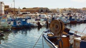 Dock méditerranéen avec de petits bateaux et personnes de pêche marchant dans la distance banque de vidéos