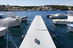 Dock in Mali Losinj, Croatia. A dock in the port of Mali Losinj, Croatia, with traditional fishing boats and flippers left by a fisherman Royalty Free Stock Image