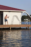 Dock Man. A man is doing a back flip off the end of a dock into the water Stock Image