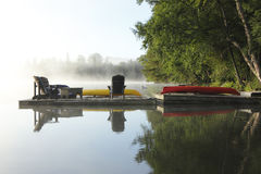 Dock on a Misty Lake. Dock with Chairs, Canoe and Kayak on a Misty Morning - Haliburton, Ontario, Canada stock images