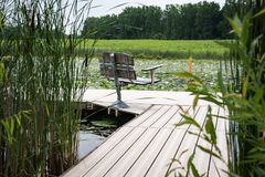 Dock mit Bank auf kleinem Teich Stockfotos