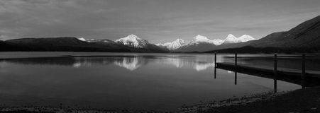 A Dock And Mountains Reflected In A Lake In Black And White Royalty Free Stock Photography