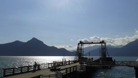 Dock and moutains undet the sun Royalty Free Stock Image