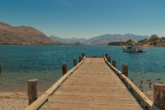 Dock on New Zealand mountain lake. Wooden dock on a calm blue mountain lake in South Island, New Zealand Royalty Free Stock Photo