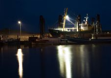 Dock at Night. Cutter in a dock at a calm night, flooded with light Stock Photos