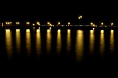 Dock at nighttime. With reflecting lights in the water Royalty Free Stock Image