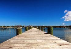 Dock On Ocean Bay. A wide angle perspective of a small wooden dock looking out onto a small ocean bay Royalty Free Stock Photography