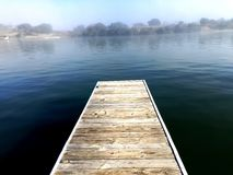 Dock overlooking calm fog over the river Stock Photo