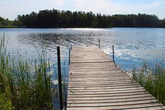 Dock overlooking a lake with trees in the background stock photography