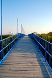 Dock path to the sea. With colorful blue handhelds royalty free stock image