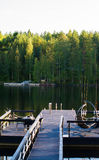 Dock or pier on lake in summer day. forest,  Finland Royalty Free Stock Photos