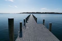 Dock perspective with room for copy. A dock or pier perspective on a lake with a strong horizon concept of relaxation or vacation with nobody around. Room for royalty free stock image