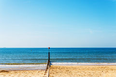 Dock pilings on a sandy beach, blue ocean and yellow sand, sunny Royalty Free Stock Images