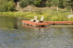 Dock by a pond. Two log chairs on a red deck by a small pond Stock Images