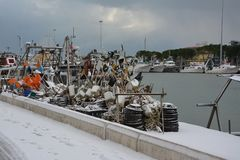 Ships and fishing nets still on the harbor`s quay in winter with snow stock image