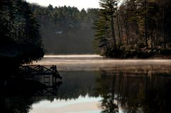 A dock reflects in calm lake water in a misty sunrise in Western royalty free stock images